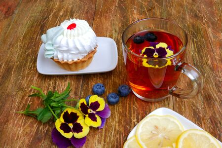 Tasty fresh cake on saucer, on wooden table. On table there is also cup with tea, pansy flowers and saucer with lemon. Close-up. Stock Photo