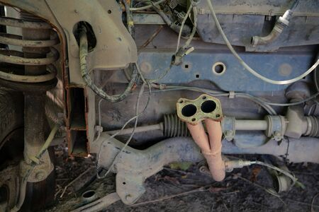 Parts of an old rusty abandoned car. Various disassembled parts and mechanisms. Outdoors.