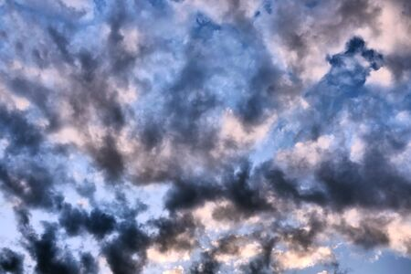 Big dark dramatic fluffy clouds in the blue sky on sunny light. Abstract nature background. Close-up.