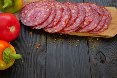Homemade fast food. Making sandwich. Sliced salami and ripe vegetables lie on dark wooden table. For the preparation of sandwich with sausage. On dark wooden background. Close-up.