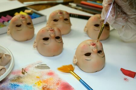 Making dolls. Master painter carefully paints lips of blank for doll with thin brush. Concept of combining work and hobbies. Indoors.