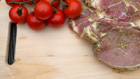 Pork or beef steaks, pickled in spices for frying, and cherry tomatoes on branch, lie on the kitchen board. Close-up.
