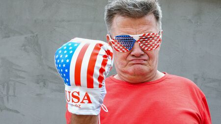 Brutal, proud, caucasian ethnicity senior man in glasses in the colors of American flag. He threatens someone with his fist in boxing glove. Close-up.