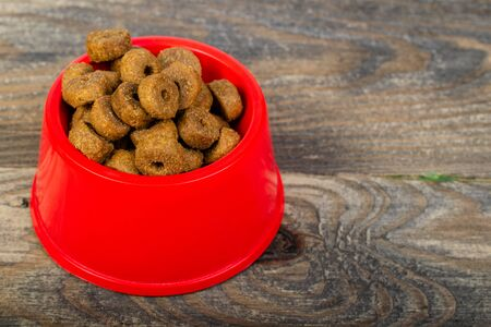 Dry crispy cat food in red plastic bowl, which is located on wooden floor or table. Close-up.