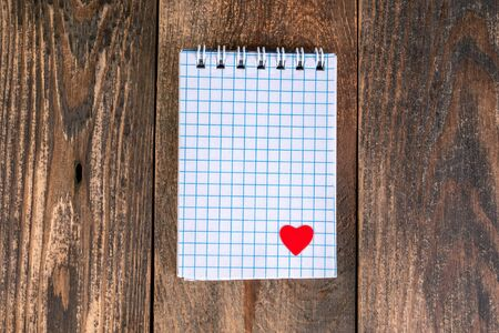 Notepad in cage, with small heart in lower corner lies on wooden table. The concept of Valentines day holiday or reminder of love to someone. Copy space. Top view. Close-up.