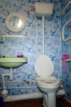 Interior of old house. Outdated toilet with high drain tank and wash basin in bathroom in residential building. Indoors.