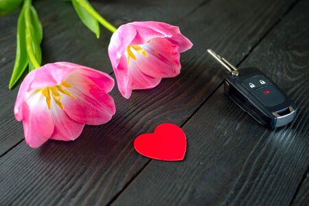 Two pink tulip flowers, car keys and red paper heart lie on dark wooden table. The concept of romantic gift and love. Selective focus. Close-up.