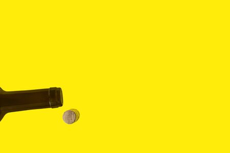 Brown neck of wine bottle . Cork from bottle. Isolated on yellow background. Flat lay, top view. Lay out.