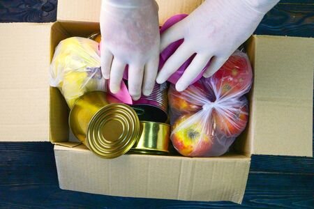 Packed various food items in donation box for the poor. Canned food, cooking oil, eggs, fruits, pasta. Top view, flat lay. Close-up. Indoors.
