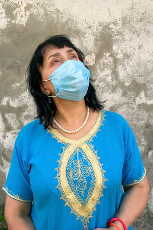 Asian or caucasian ethnicity mature woman in blue dress with medical mask on his face to protect COVID-19, looking up against background of gray plastered wall. Vertical shot. Close-up.