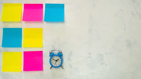 Set of several blank colorful post notes with copy space for text on light background. Blue alarm clock. Concept prepare for teamwork or brainstorming. Top view. Flat lay. Close-up. Indoors. Archivio Fotografico