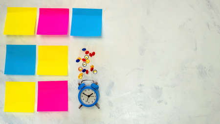 Several blank colorful   notes with copy space for text on light background. Blue alarm clock, push pins. Concept prepare for teamwork or brainstorming. Top view. Flat lay. Close-up. Indoors.