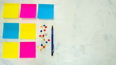 Set of several blank colorful  notes with copy space for text on light background. Concept prepare for teamwork or brainstorming. Pen, push pins. Top view. Flat lay. Close-up. Indoors.