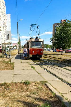 Kiev, Ukraine, August 2020: - Tram stop and city tram that stopped to disembark passengers who wear protective medical masks during coronavirus pandemic. Vertical format. Overall plan. Outdoors. Editoriali