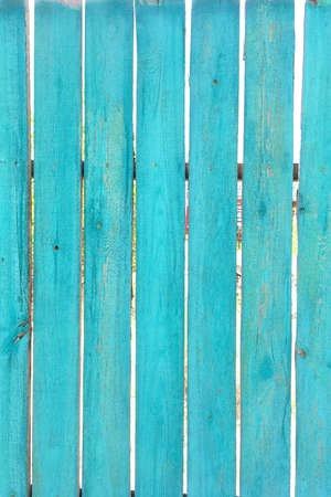 Old natural turquoise wooden fences boards as great background or texture. Vertical format. Close-up. Outdoors.