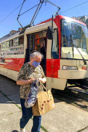 Kiev, Ukraine, August 2020: - typical tram stop and city tram that stopped disembark passengers who wear protective medical masks during coronavirus pandemic. Vertical format. Close-up. Outdoors. Editoriali