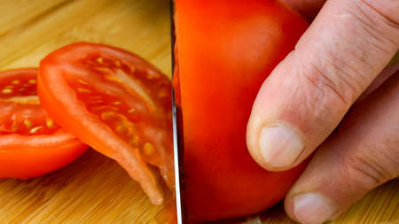 Chefs hands are cutting juicy ripe tomato with kitchen knife on wooden cutting board. Close-up. 16x9 format. Indoors.