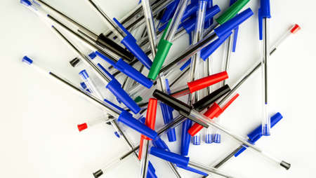 Pile of a lot multi colored plastic ballpoint pens on white background. Abstract stationery background. Top view. Close-up. Many objects.