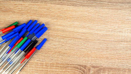 Pile of a lot multi colored plastic ballpoint pens on wooden table. Abstract stationery background. Top view, flat lay. Copy space for text. 16x9 format. Top view. Close-up. Many objects.