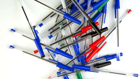 Pile of a lot multi colored plastic ballpoint pens on white background. Abstract stationery background. 16x9 format. Top view. Close-up. Many objects. Archivio Fotografico