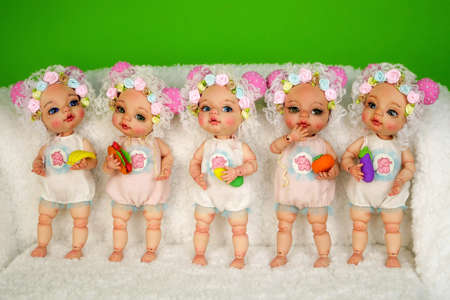 Collection of adorable handcrafted ball-jointed dolls that stand in a row on shaggy white surface and face different directions. Close-up. Indoors.