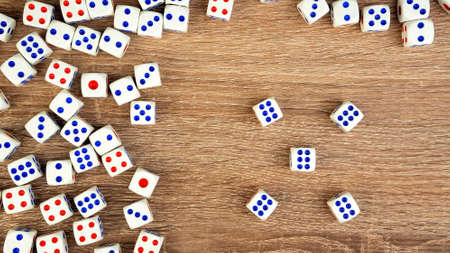Many white dice with red and blue dots on wooden table. Casino gambling concept. Close-up. Indoors. Archivio Fotografico