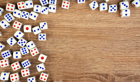 Many white dice with red and blue dots on wooden table. Casino gambling concept. Copy space for text. Close-up. Indoors.