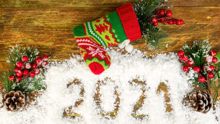 Christmas branches with berries and cones in decorative snow, which says 2021 and knitted Christmas stocking or Santas boot. Christmas mood concept. Top view. Flat lay. Close-up. Festive.