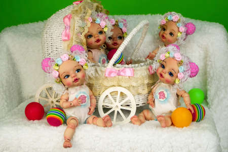 Collection of adorable handcrafted ball-jointed dolls that sits in decorative baby carriage on shaggy white surface and face different directions. Selective focus. Close-up. Indoors.