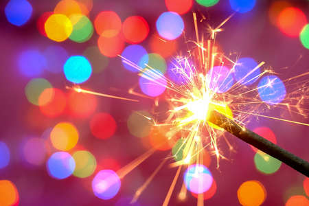 Bright burning sparkler against the backdrop of defocused multicolored garland. Blurred backdrop. Merry Christmas or birthday holiday concept. Close-up. Abstract.