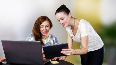 Two young smiling women in casual clothes are working or having fun near their laptop. Work from home or have fun on social media. Close-up. Indoors. Archivio Fotografico