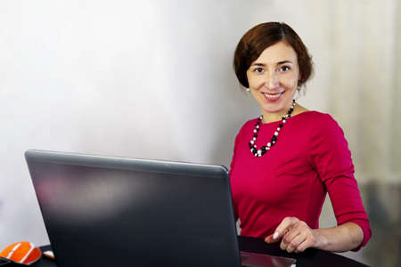 Portrait of smiling woman in casual clothing working on laptop at home office at home based business and looking at camera. Close-up. Indoors.