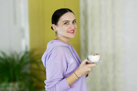 Portrait of smiling young woman in casual clothing which standing alone in room and holding white coffee cup and looking at camera. Close-up. Indoors.