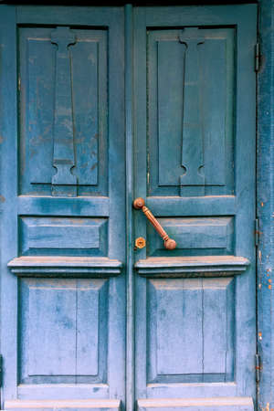 Old blue door with brass handle in abandoned ancient house. Close-up. Outdoors.