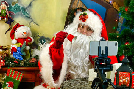 Cheerful Santa Claus congratulates remotely with video calling on Christmas and New Year holidays in online chat during self-isolation in quarantine. Close-up. Holiday.