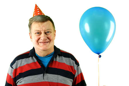 Mature adult man of Caucasian ethnicity in casual clothes and birthday cap with air helium balloon, smiling and rejoicing. Cut out on white background. Medium plan. Indoors.
