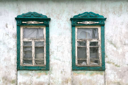 Two wooden windows in abandoned old countryside house. View of an old-fashioned house in the village. Close-up.