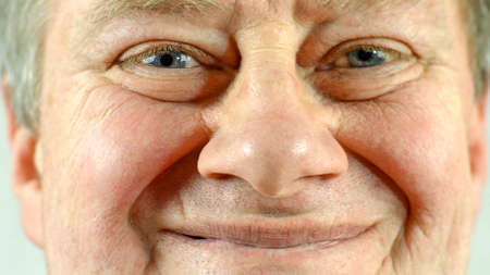 Front portrait of mature adult mans face which smiling. Wrinkle skin and gray eye, looking at camera. Selective soft focus. Close-up. Indoors. Archivio Fotografico