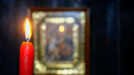 Candle burning in dark against soft focus Virgin Mary icon. Religion and spirituality. Selective focus. On dark wooden wall background. Close-up. Archivio Fotografico