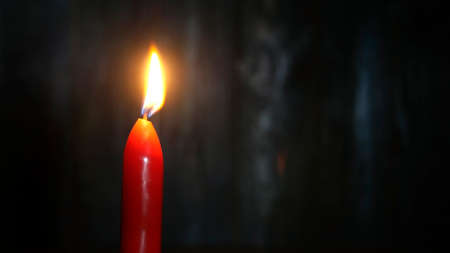 Red candle burning on dark wooden wall background. Selective focus. Copy space. Close-up. Indoors.