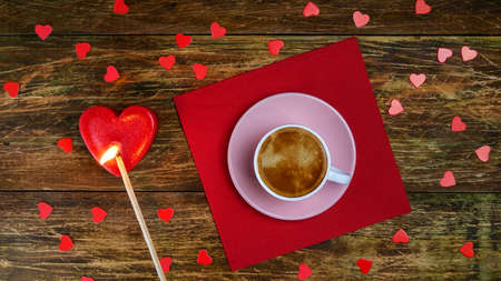 Cup of coffee on red napkin and set fire heart-shaped candle with long match. A romantic day. Valentines day or womens day concept. Top view. Flat lay. Close-up. Indoors.