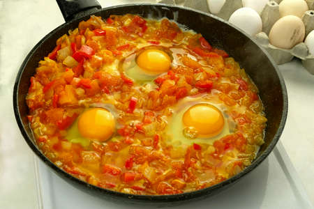 Cooking fried eggs shakshuka in vegetables sauce in frying pan. Jewish and arabic cuisine. Shakshuka recipe. Close-up. Indoors.