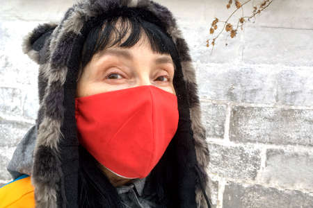 Portrait of mature adult woman in face mask and warm clothes during pandemic coronavirus, Covid-19. On brick background. Close-up. Outdoors. Archivio Fotografico