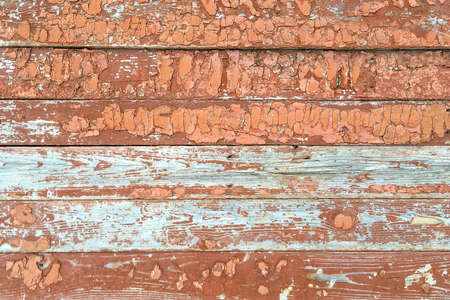 Brown and white wooden background with peeling paint. Use as text place. Old fence. Close-up. Outdoors.