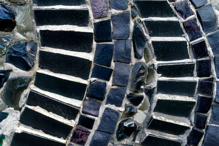 Black and white abstract tile mosaic wall or floor as decorative background. Soft focus. Close-up. Outdoors.