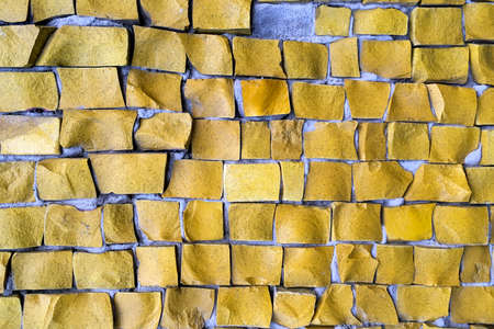 Yellow or brown abstract tile mosaic wall or floor as decorative background. Soft focus. Close-up. Outdoors. Archivio Fotografico