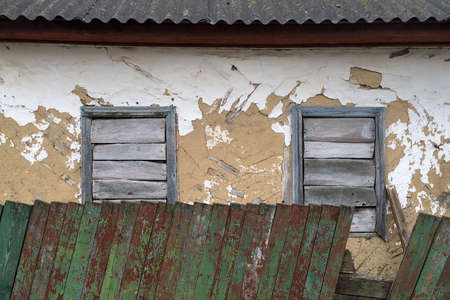 Facade of abandoned crumbling mud house in a village with boarded up windows behind a green wooden fence. Close-up. Outdoors. Editoriali