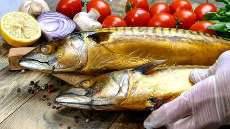 Delicious smoked fish mackerel on a wooden table next to the cherry tomatoes, onion, mushrooms and parsley. Healthy Mediterranean food recipe. Close-up. Indoors.