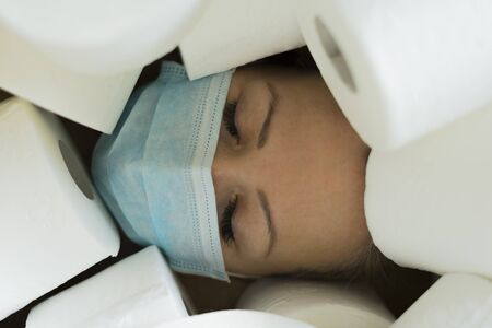 Close-up of beautiful woman with closed eyes in medical mask surrounded by toilet paper. Hoarding toilet paper due to COVID-19 panic, home isolation, preparing for coronovirus quarantine