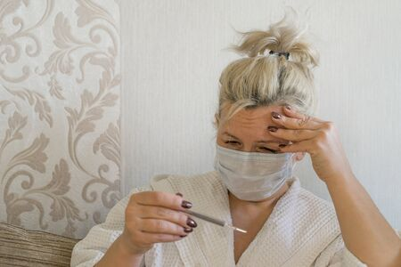 Sick woman in bed in medical mask looking at thermometer with sadness. Caucasian middle-aged woman on self-isolation during covid-19 or flu. Coronavirus epidemic concept Stockfoto